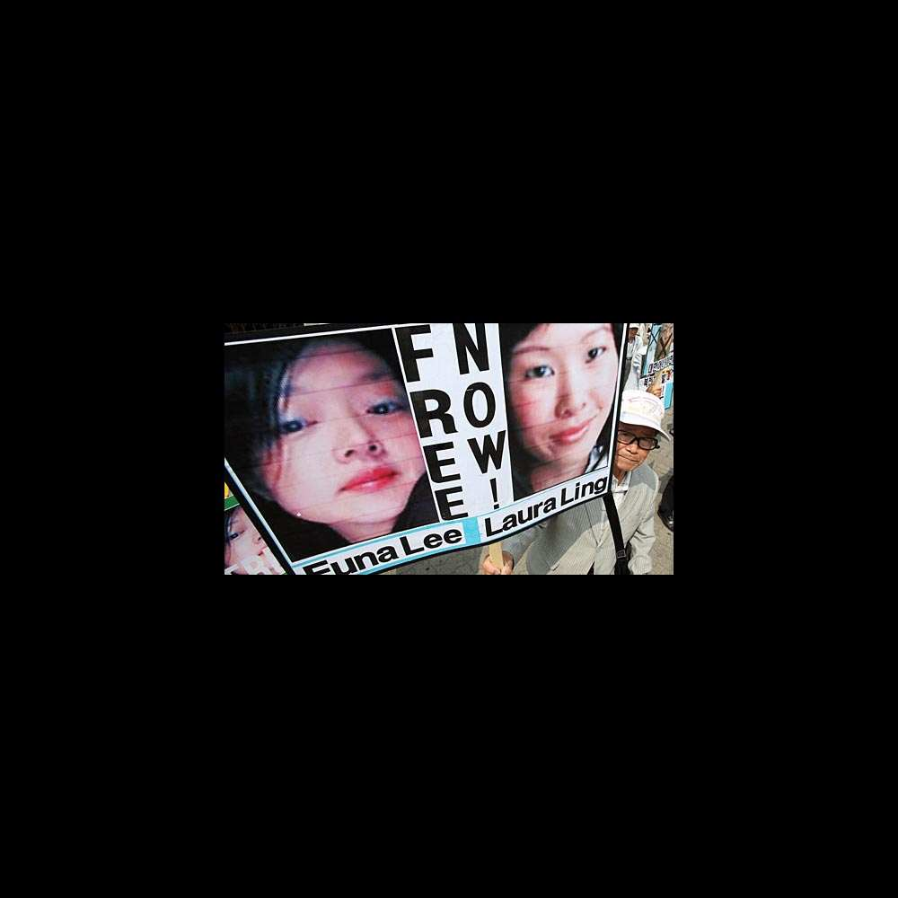 A South Korean protester displays portraits of American journalists detained in North Korea as they shout slogans during