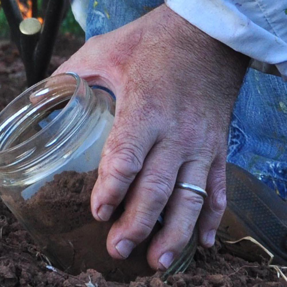 Sam Roloff\'s hand getting soil samples at Archery Summit Vineyard